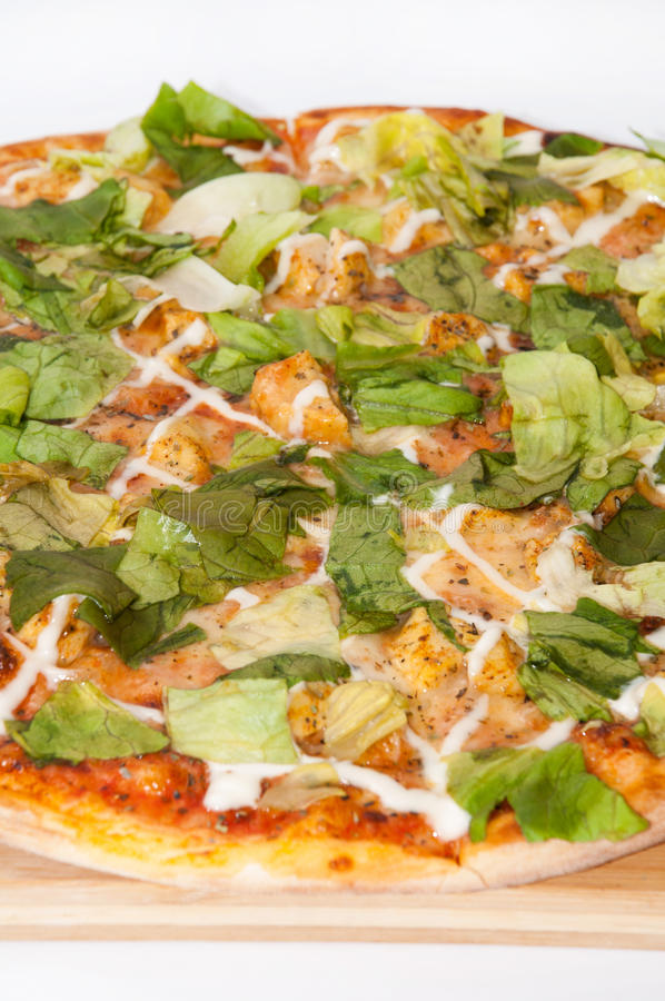 Gehele pizza met sla op een houten raad royalty-vrije stock foto