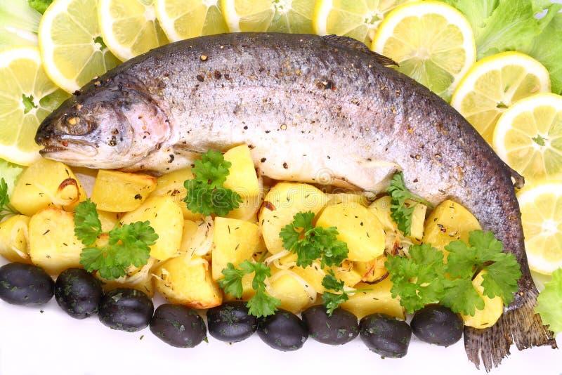 Gehele regenboogforel die met aardappels, citroenen wordt geroosterd royalty-vrije stock afbeelding