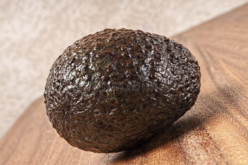 Gehele ruwe avocado, scherpe raad stock fotografie