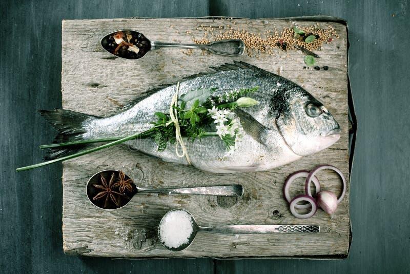 Gehele Ruwe Vissen op Scherpe Raad met Kruiden stock afbeelding