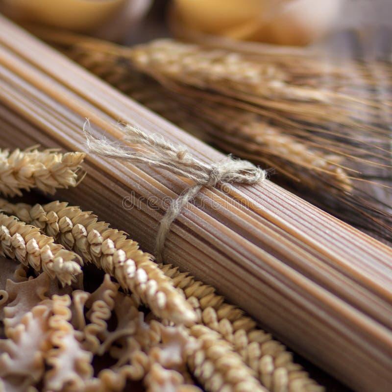 Gehele tarwe Italiaanse deegwaren met aren stock foto's