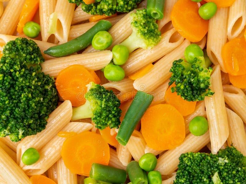 Gehele tarwedeegwaren Penne met broccoli, wortelen, groene erwten Close-up, macro Dieetmenu, juiste voeding, gezond voedsel royalty-vrije stock foto's