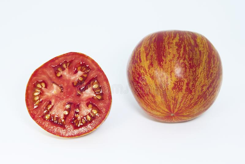 Gehele tomaat en een tomaat van de de helftbesnoeiing op een witte achtergrond Rijpe bont tomaten stock foto