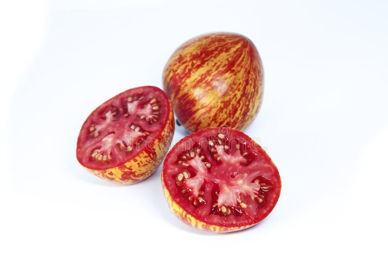 Gehele tomaat en van een de helftenbesnoeiing tomaten op een witte achtergrond Rijpe bont tomaten stock afbeelding
