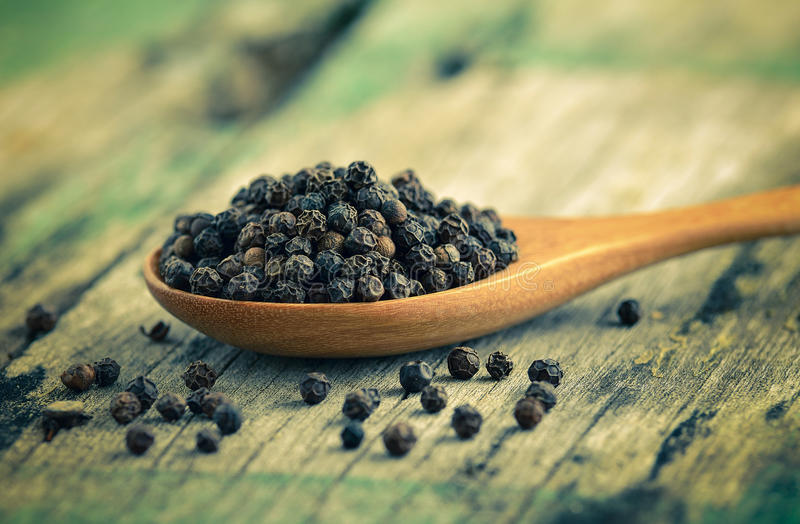 Gehele zwarte peper op houten lepel royalty-vrije stock foto's