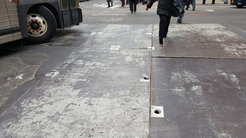 Gehen über die städtische Straße mit Busdrehen- und -metallstraße hihole Abdeckungen stockfotos