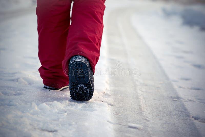 Gehen in den einfrierenden Winter auf der vereisten Straße durch Bahn von Autos in der roten Hose und in den Schneestiefeln lizenzfreies stockfoto
