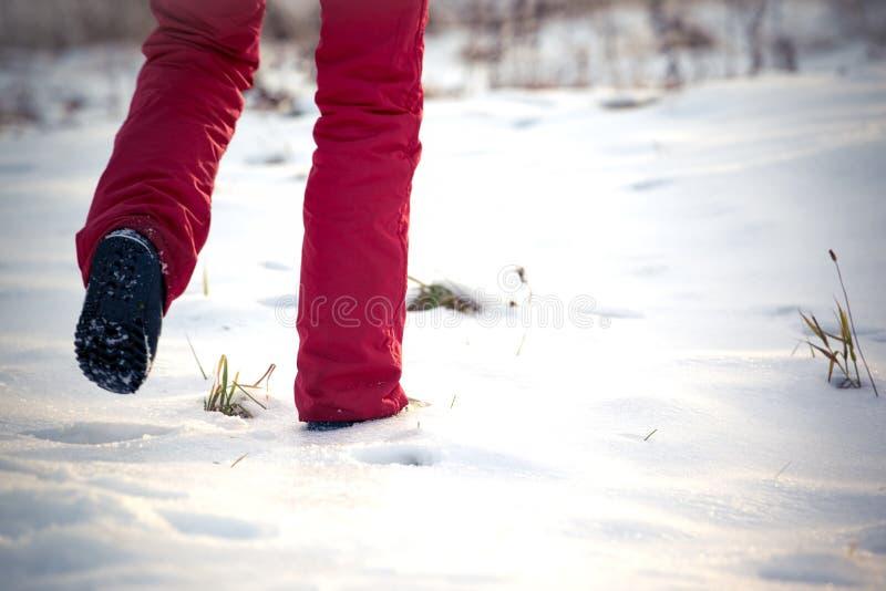 Gehen in den einfrierenden Winter auf Schnee in der roten Hose und in den Schneestiefeln stockfotografie