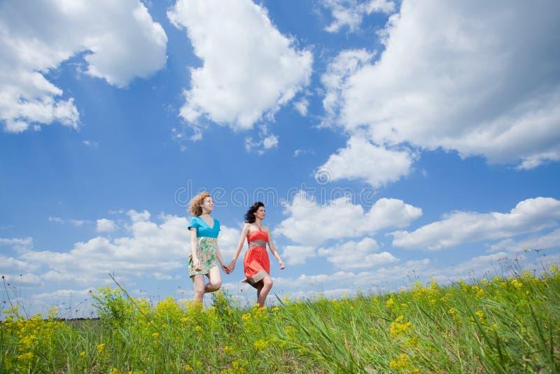 Gehen mit zwei schönes junges freundliches Frauen stockbild