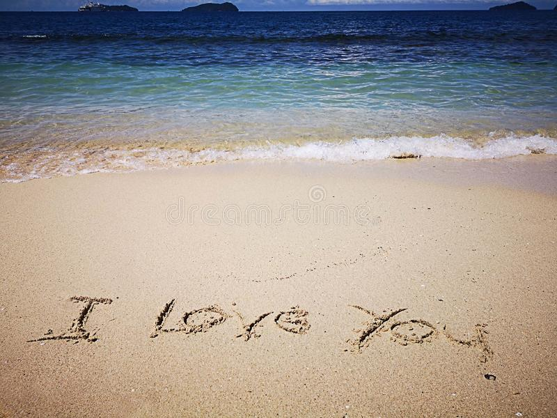 Gehen am sandigen Strand und am schönen sonnigen Tag und ich liebe dich auf den sandigen Strand geschrieben lizenzfreie stockbilder