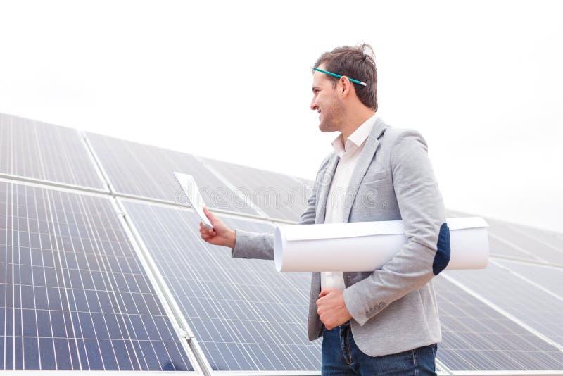 Gehen Sie mit einem Notizblock in seiner Hand und in einem aufgerollten Projekt auf einem Hintergrund von Sonnenkollektoren voran lizenzfreies stockbild