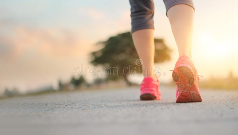 Gehende Übung der Athletenfrau auf Landstraße in Sonnenuntergang backgroun stockfotografie