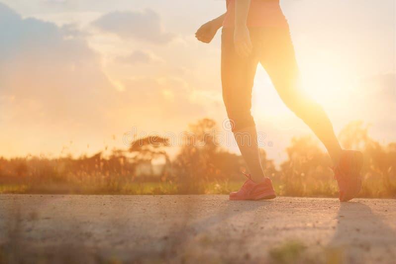 Gehende Übung der Athletenfrau auf Landstraße in Sonnenuntergang backgroun lizenzfreies stockfoto
