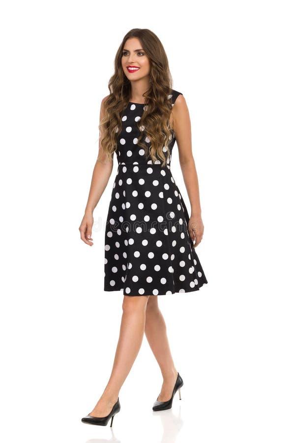 Gehende schöne junge Frau im schwarzen punktierten Cocktailkleid und den hohen Absätzen lizenzfreies stockfoto
