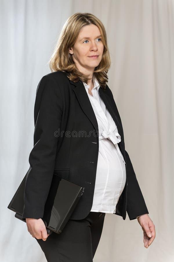 Gehende schwangere Geschäftsfrau stockfotografie