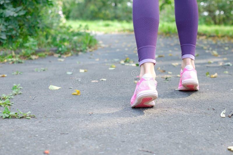 Gehende und rüttelnde Frau mit den athletischen Beinen und den Laufschuhen, Abschluss oben, Copyspace für Ihren Text stockfoto