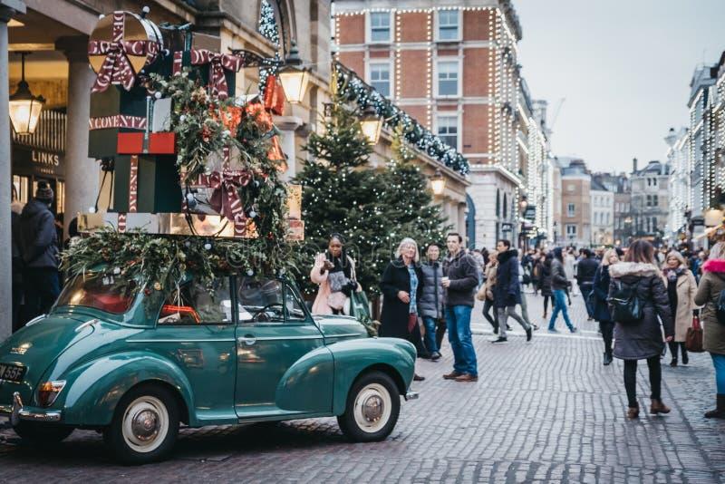 Gehende Vergangenheit der Leute und nehmen Fotos von Auto Weihnachtsdekorationen in Covent Garden-Markt, London, Großbritannien lizenzfreies stockfoto