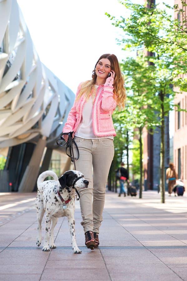 Gehender Hund der Frau und Unterhaltung mit Freunden am Handy lizenzfreie stockbilder