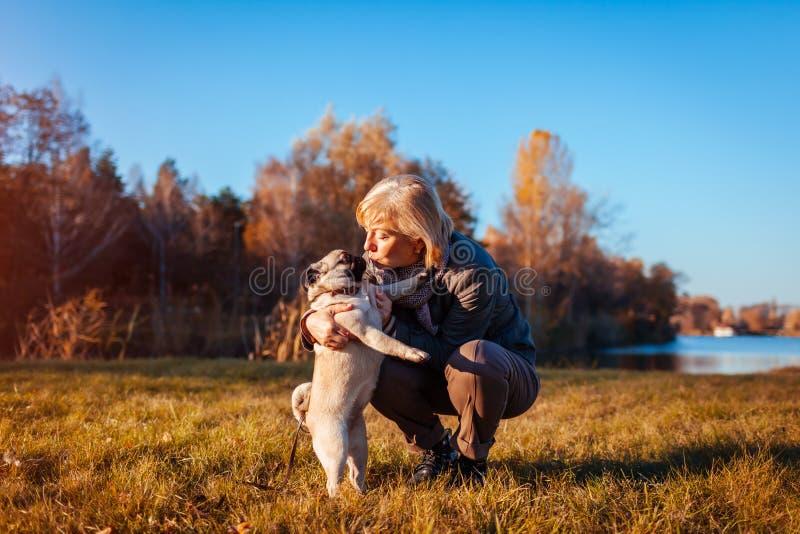 Gehender Pugvorlagenhund im Herbstpark durch Fluss Glückliche Frau, die Haustier umarmt und küsst stockfotografie