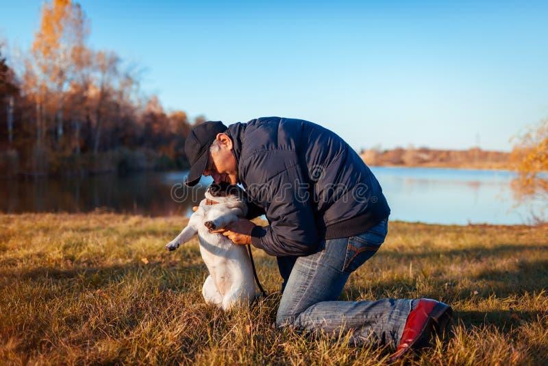 Gehender Pugvorlagenhund im Herbstpark durch Fluss Glücklicher Mann, der draußen Haustier umarmt lizenzfreie stockbilder