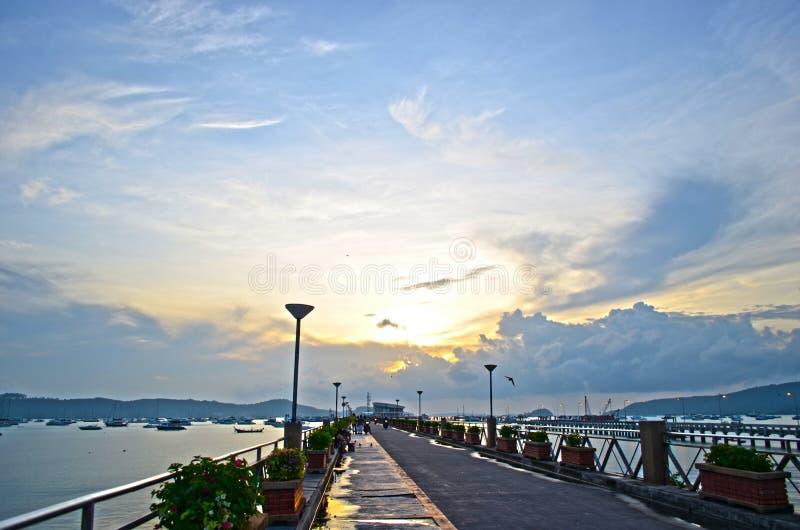 Gehender und aufpassender schöner Sonnenuntergang auf Pier stockbild