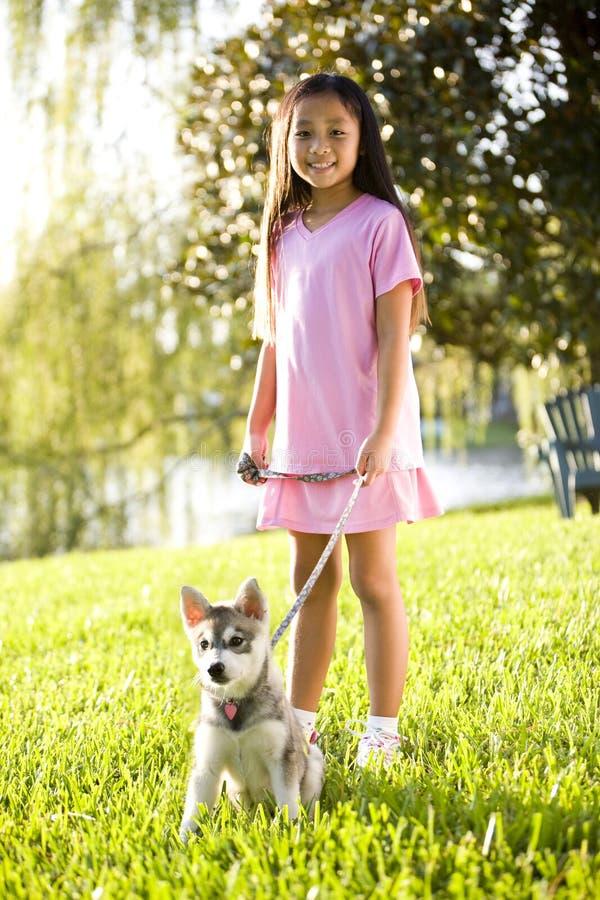 Gehender Welpe des jungen asiatischen Mädchens auf Leine auf Gras stockbild