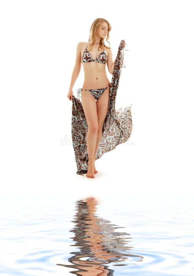 Gehendes Bikinimädchen mit Sarong auf weißem Sand stockbilder