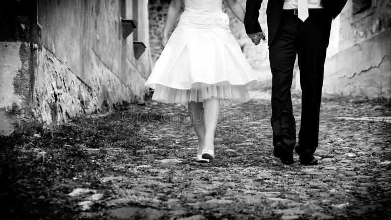 Gehendes Händchenhalten der Braut u. des Bräutigams stockfoto