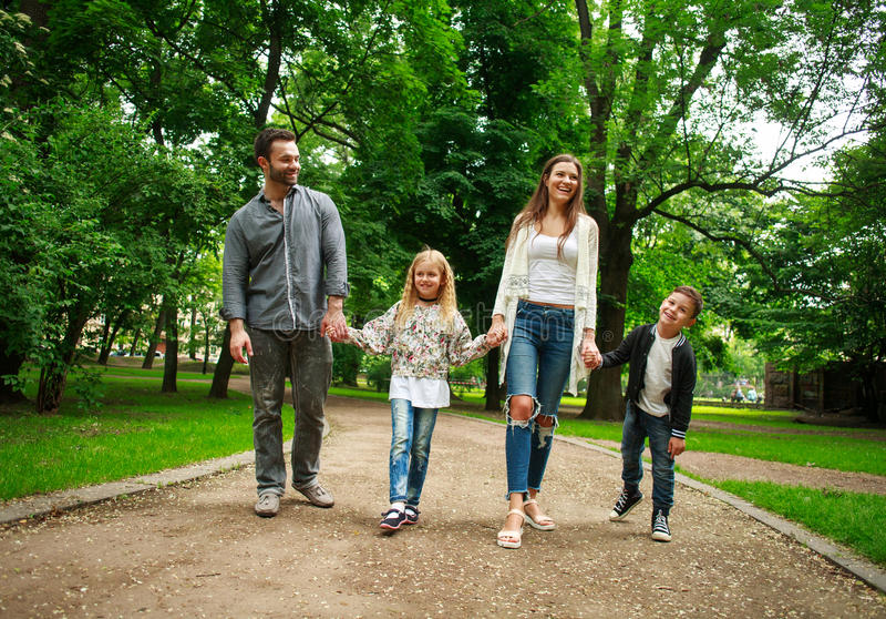 Gehendes Händchenhalten der glücklichen Familie im grünen Stadtpark stockfotografie