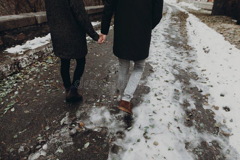 Gehendes Händchenhalten der stilvollen Hippie-Paare im Herbstpark Fas lizenzfreie stockfotos