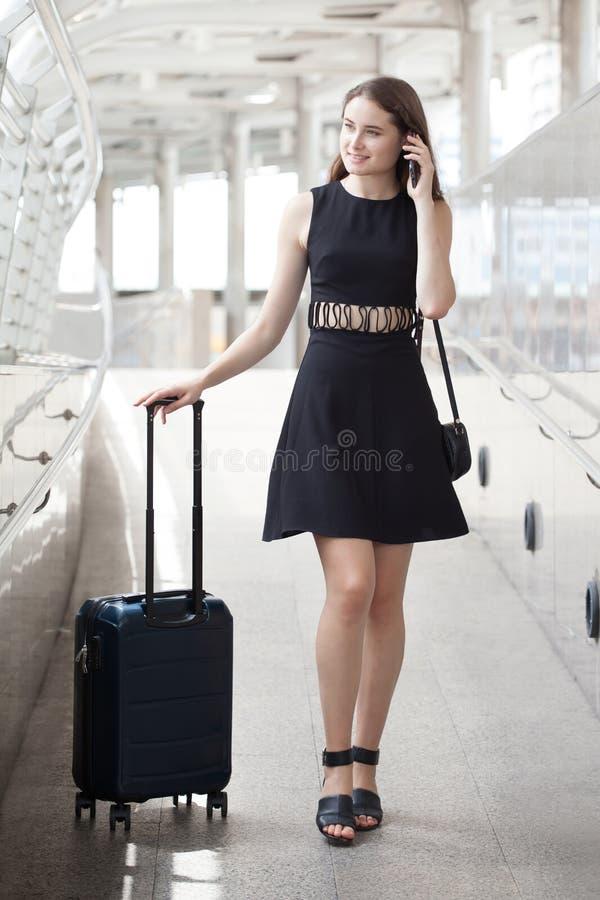 gehendes und tragendes Handgepäck der glücklichen jungen Geschäftsfrau unter Verwendung des Handys reisendes Mädchen mit Koffer u lizenzfreies stockbild
