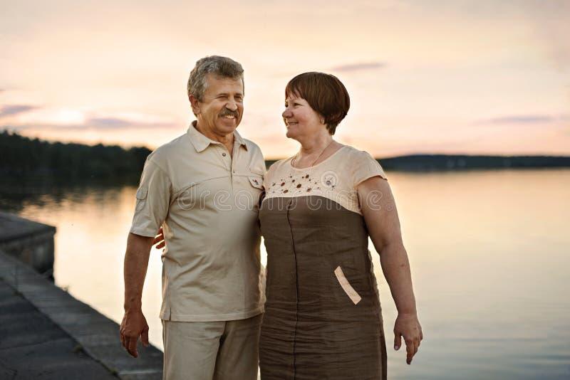 Gehendes Unterhaltungsc$lachen der älteren Paare bei dem Sonnenuntergang nahe dem Seefluß lizenzfreie stockfotografie