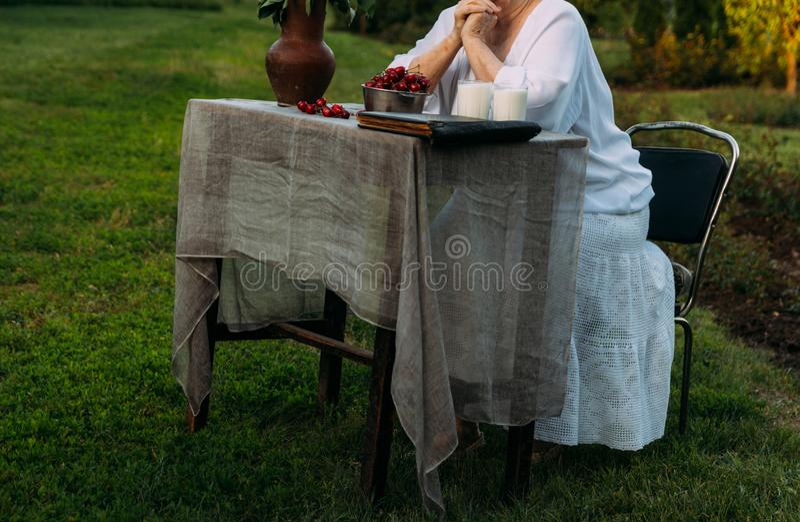Geheugen van de bejaarden grootmoederzitting als voorzitter in de tuin op de lijst zijn er twee glazen melk, een plaat met a stock afbeeldingen
