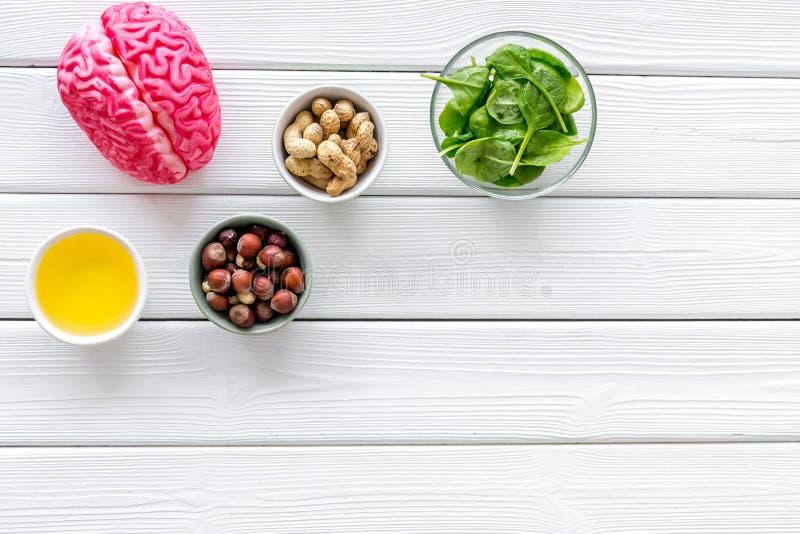 Gehirnnahrungsmittelkonzept mit Erdnuss, Haselnuss, Samenöl, spinage auf weißem hölzernem copyspace Draufsicht des Hintergrundes lizenzfreies stockbild