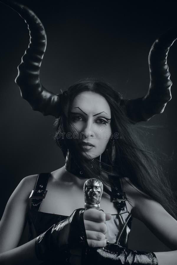Gehoornd duivels meisje met zwaard stock foto's
