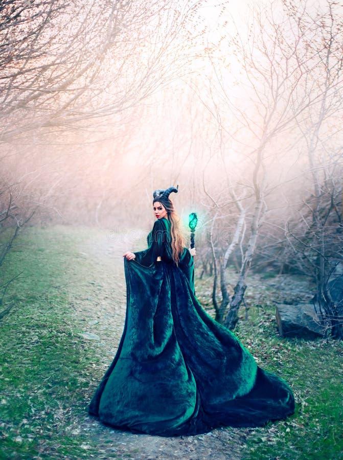 Gehoornde vreemdeling in lange smaragdgroene zijdekleding diep in bos alleen met magische in hand stok, het vreselijke vampier ve stock afbeeldingen