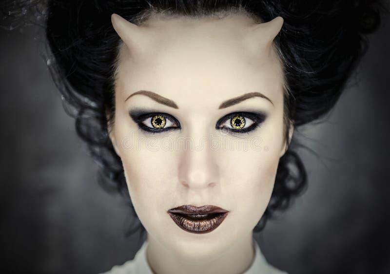 Gehoornde vrouw met heldere make-up stock foto's