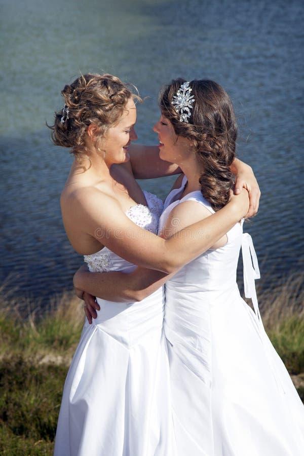 Gehuwd enkel gelukkig lesbisch paar in witte kleding dichtbij klein meer royalty-vrije stock afbeeldingen