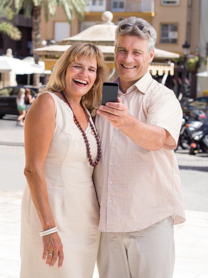 Gehuwd rijp paar van reizigers die voor een selfiefoto stellen in tropische stad royalty-vrije stock afbeeldingen