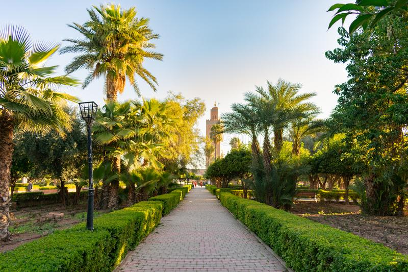 Gehweg bei Parc Lalla Hasna in Marrakesch Marokko mit Koutoubia-Moschee im Hintergrund stockfotos
