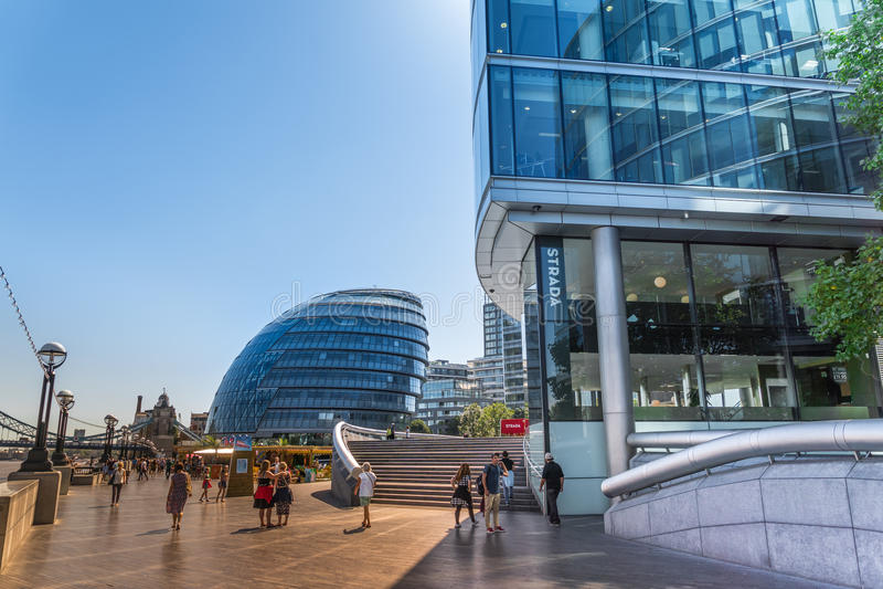 Gehweg am southwark hat mit Leuten und Ansicht des modernen Gebäudes des Rathauses und der Bürogebäude auf der Themse in London e lizenzfreie stockfotografie