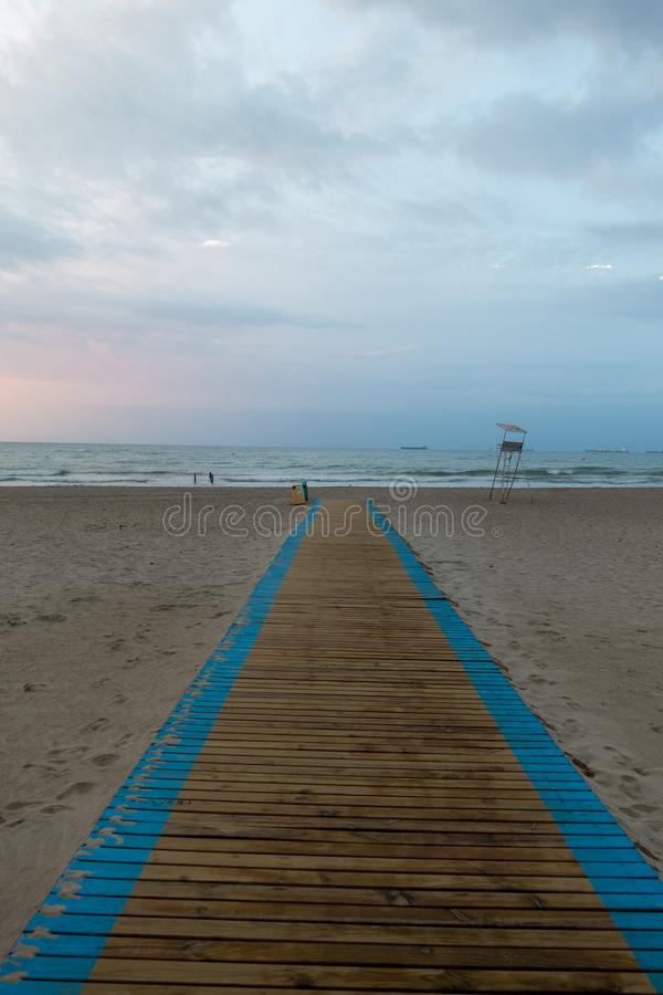 Gehweg zum Strand in einem schönen Sonnenaufgang stockfoto