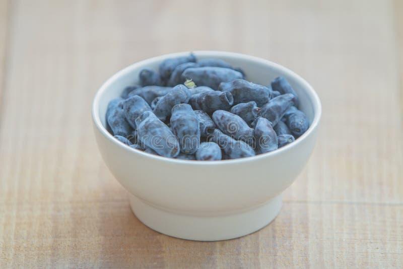 Geißblatt blaue berryHoneyberries, Jungfernrebe, woodbind auf weißer Platte auf Holztisch lizenzfreies stockfoto
