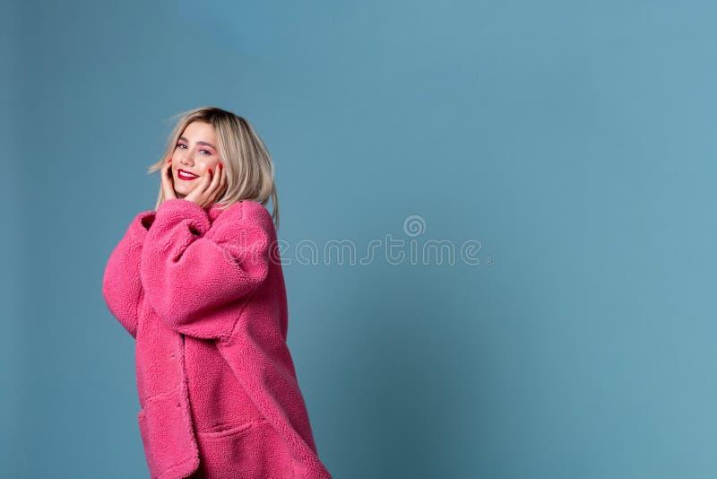 Geinteresseerd jong meisje die in modieuze roze laag camera bekijken stock foto