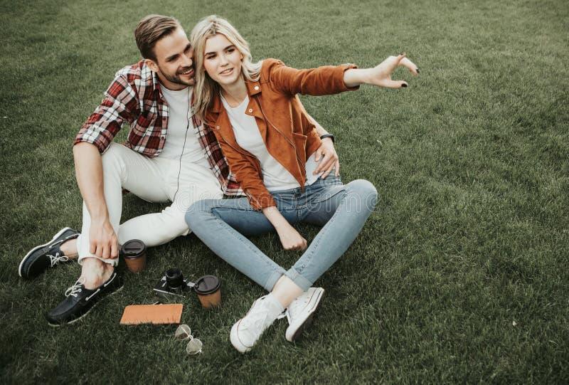 Geinteresseerd jong paar die picknick op groen gras hebben royalty-vrije stock foto