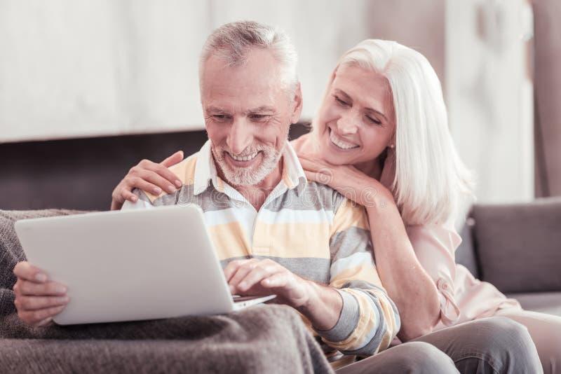 Geinteresseerd oud paar die en met laptop glimlachen werken stock foto's