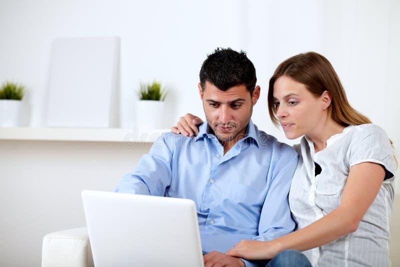 Geinteresseerd paar dat op laptop doorbladert royalty-vrije stock afbeelding