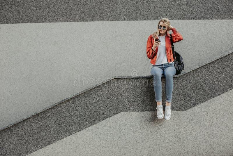 Geinteresseerde jonge vrouw die actief moderne smartphone gebruiken stock foto