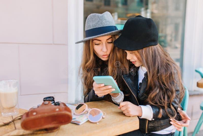 Geinteresseerde jonge vrouw die in vilten hoed blauwe smartphone bekijken die holdingsmeisje in leerjasje Portret van royalty-vrije stock foto's