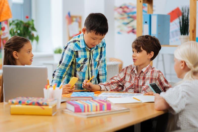 Geinteresseerde kinderen die schoolkwesties samen in een klaslokaal bespreken royalty-vrije stock foto